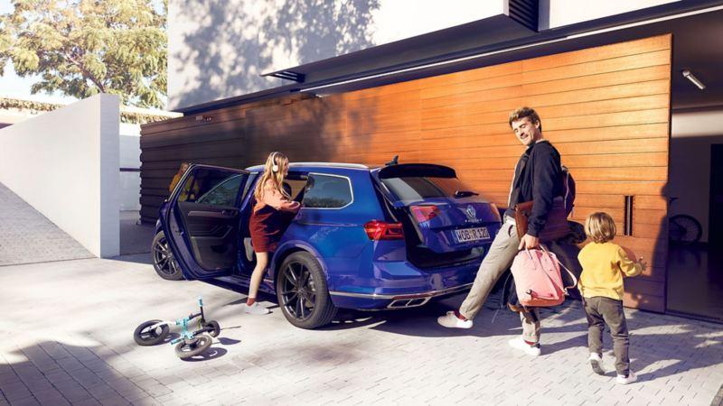 En man öppnar bagageluckan på kombibilen VW Passat sportscombi