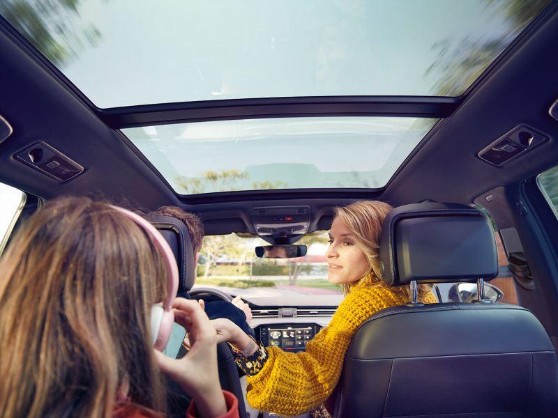 Νέο Volkswagen Passat Πανοραμική ανακλινόμενη/συρόμενη οροφή, όψη από τον πίσω πάγκο καθισμάτων προς τα εμπρός, μια γυναίκα γυρνάει σε ένα παιδί με ακουστικά