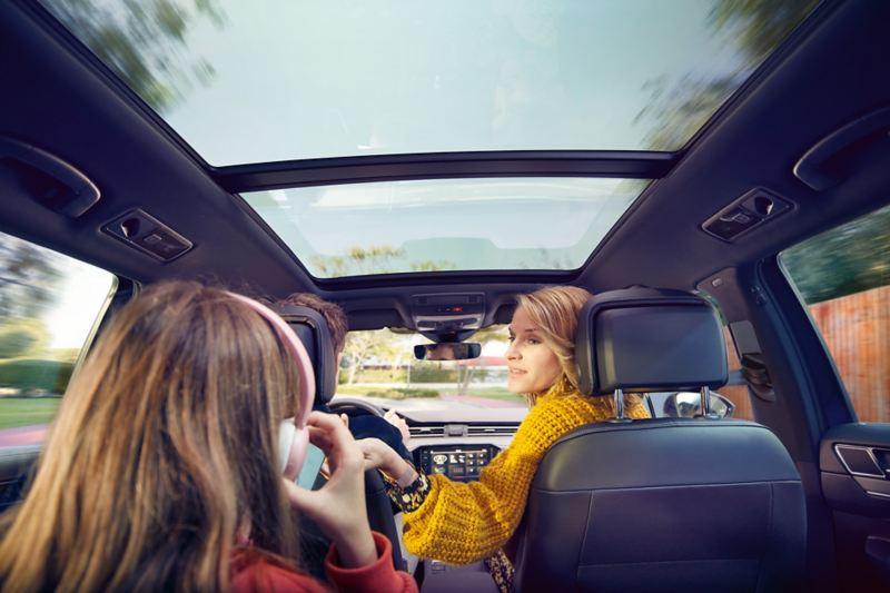 Passat Panorama-Ausstell-/Schiebedach, Blick von der Rücksitzbank nach vorn, Frau dreht sich zu Kind mit Kopfhörer um