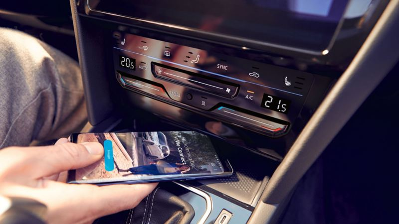 "Passat telephone interface ""Comfort"", one hand places a smartphone in the compartment for inductive charging, the We Connect Home screen can be seen on the smartphone's display"
