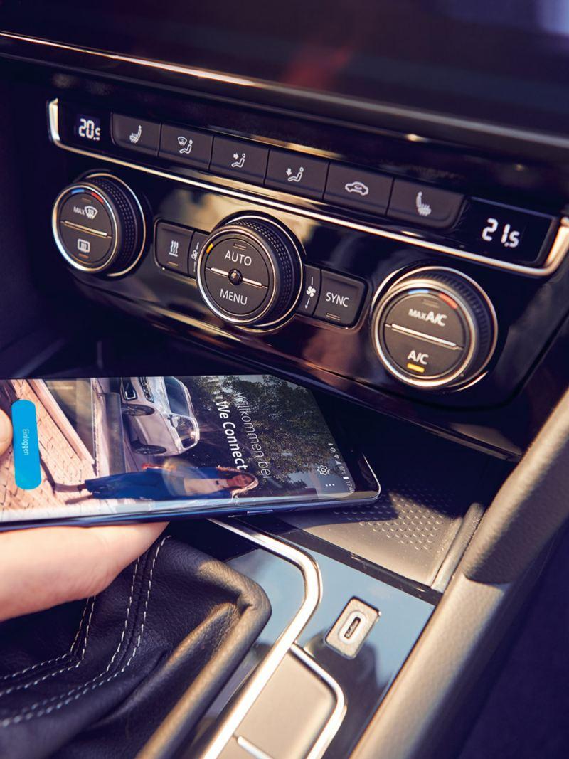 VW Passat Telefonschnittstelle «Comfort», eine Hand legt ein Smartphone in das Fach zum induktiven Laden, auf dem Display des Smartphones ist der We Connect Home-Screen zu sehen
