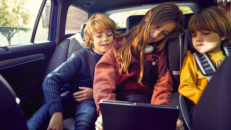 Tre bambini sono seduti sul divano posteriore di Passat e guardano un tablet, tenuto dalla bambina che occupa il sedile centrale