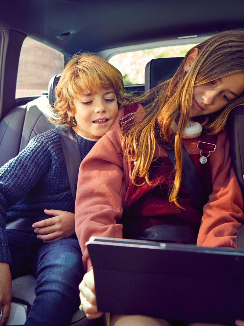 Drei Kinder sitzen im VW Passat auf der Rücksitzbank und schauen auf ein Tablet, das vom Kind auf dem mittleren Platz gehalten wird.