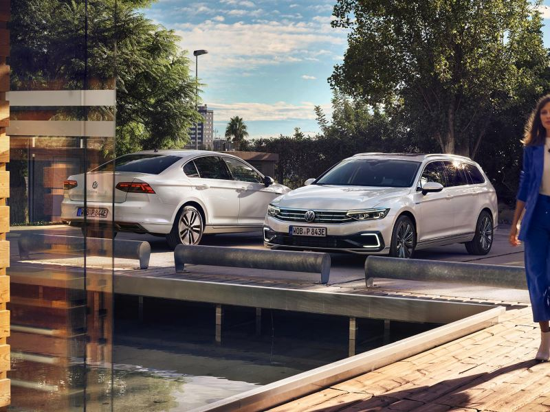 Nuova Passat GTE berlina (vista posteriore) e Passat GTE Variant (vista anteriore) una accanto all'altra in un parcheggio, una donna d'affari si dirige dal parcheggio verso un edificio