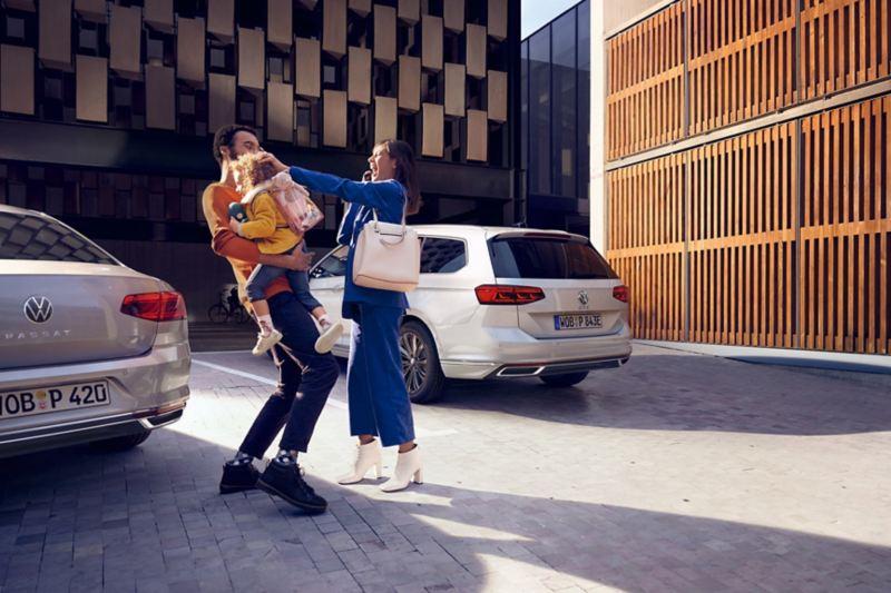 VW Passat GTE, VW Passat GTE Variant, Heckansicht auf einem Parkplatz, im Vordergrund lachende Familie