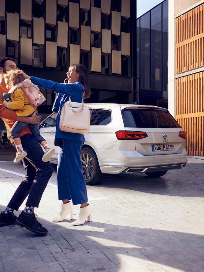 VW Passat GTE, VW Passat GTE Sportscombi, bakifrån på parkeringsplats, skrattande familj i förgrunden.