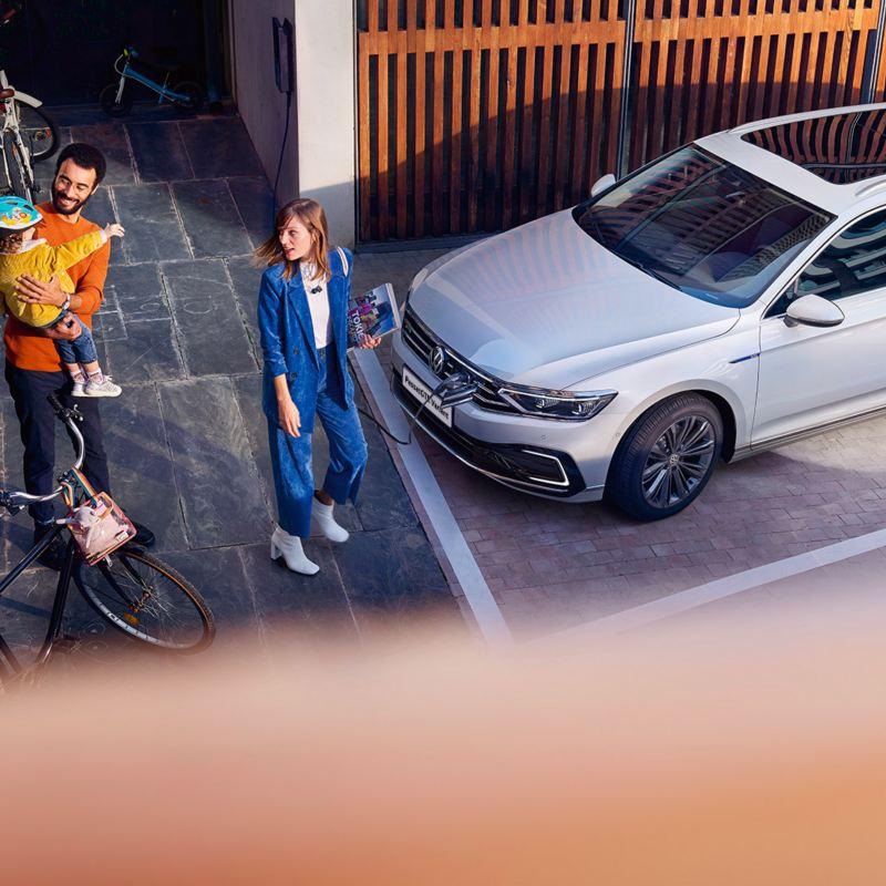 Nuova Passat Variant GTE Variant: vista dall'esterno (dall'alto in obliquo) in un parcheggio davanti a una parete di legno, una famiglia sul marciapiede