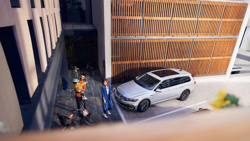 VW Passat GTE Variant set udefra og oppefra holdende på en parkeringsplads foran en træbeklædt væg, familie på sti