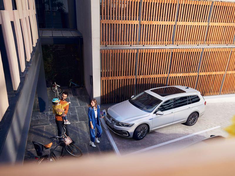 Blick von oben auf den VW Passat GTE, links daneben eine Familie