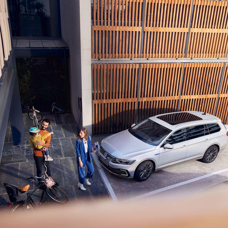 Vue d'en haut de l'extérieur d'une VW Passat GTE Variant stationnée en oblique devant une paroi en bois, une famille marche sur le trottoir