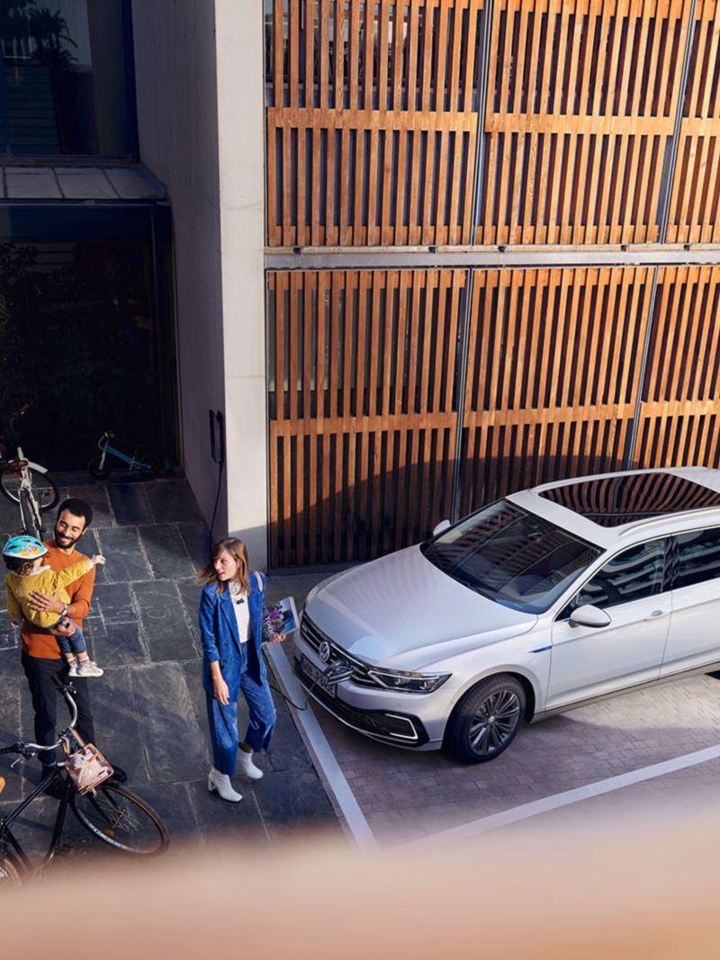VW Passat Variant GTE ukośnie od górny na parkingu przed drewnianą ścianą, rodzina na chodniku
