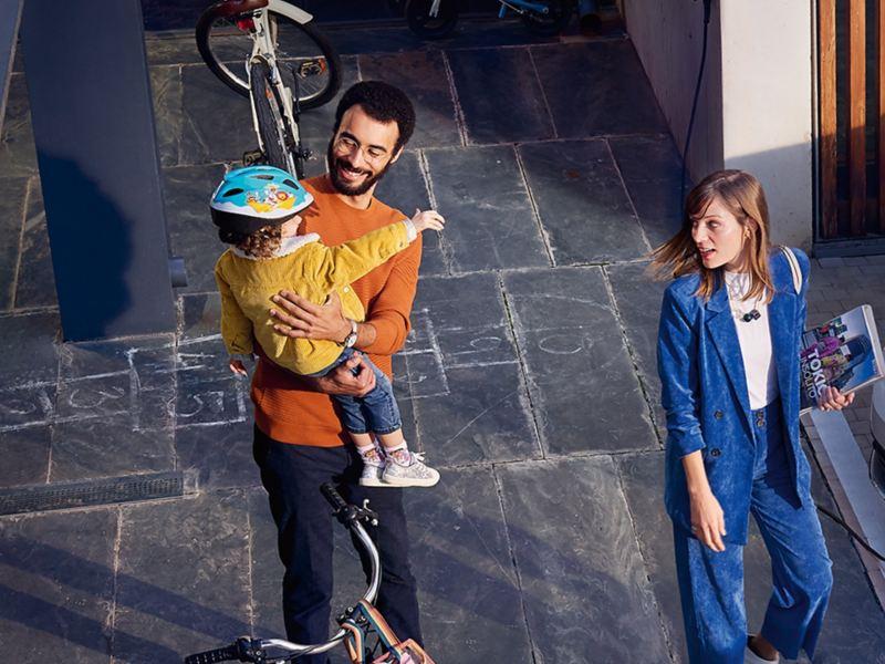 Una bambina in braccio al padre saluta una donna che passa, sullo sfondo ci sono delle biciclette.