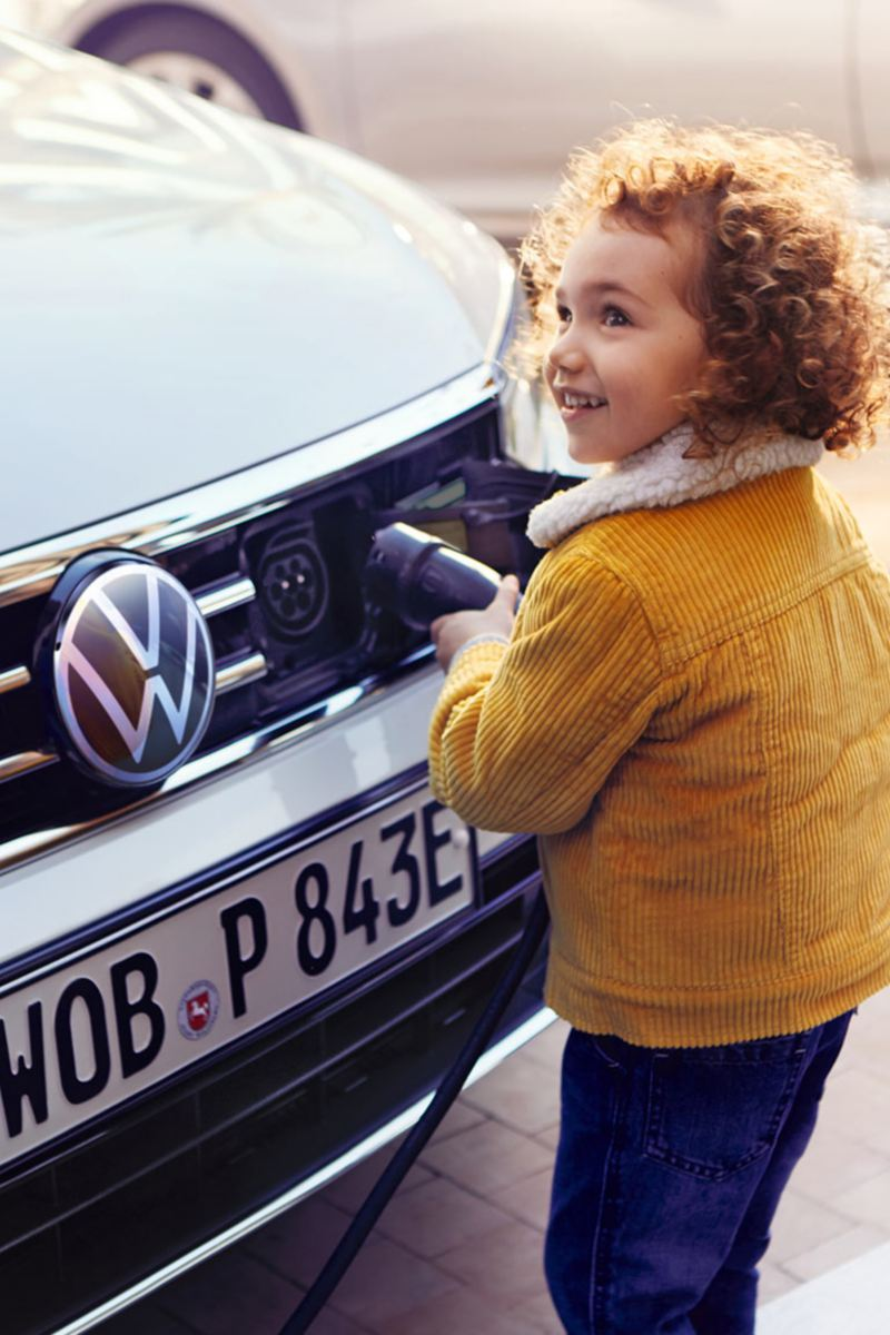 VW Passat GTE front, charging process, child pulls charging nozzle out of car