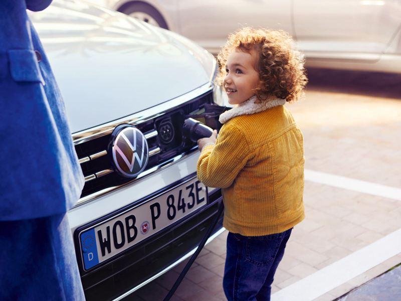 VW Passat GTE Front, Ladevorgang, Kind zieht Ladestutzen aus dem Auto