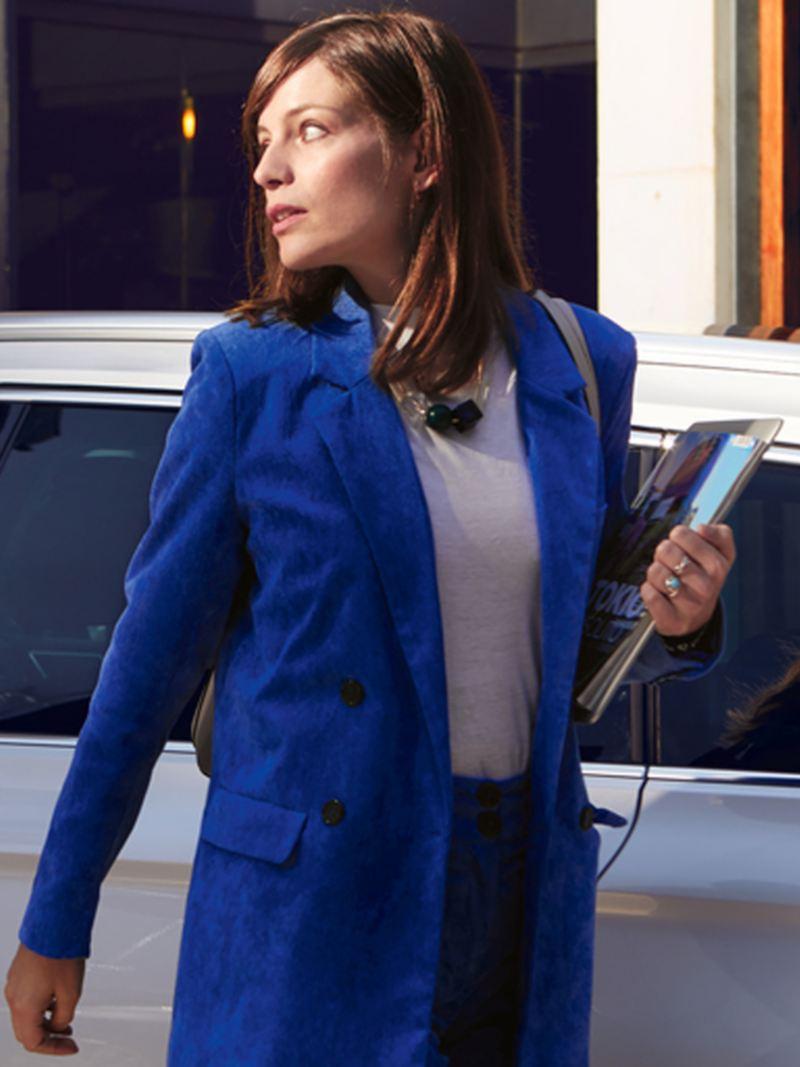 Donna viene distratta passando a fianco ad una VW Passat Variant GTE in un parcheggio
