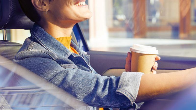 Kvinna som sitter på förarsidan i en Volkswagen och dricker kaffe