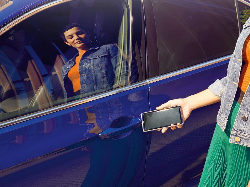 Frau öffnet Fahrertür eines blauen VW Passat mit Smartphone via mobiler Schlüssel