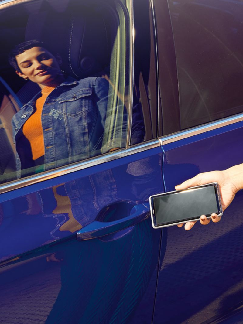"""Passat telephone interface """"Comfort"""", one hand places a smartphone in the compartment for inductive charging, the We Connect Home screen can be seen on the smartphone's display"""