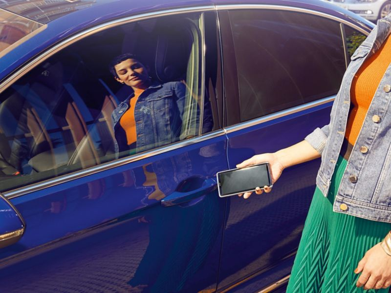 VW Passat exterior, mobile key Woman opens the car with the smartphone