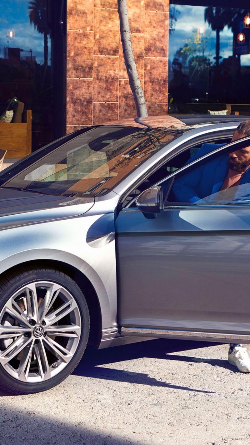 """Passat berlina Elegance in argento Pyrit con cerchi """"Verona"""", vista frontale-laterale, un uomo scende dalla sua auto"""