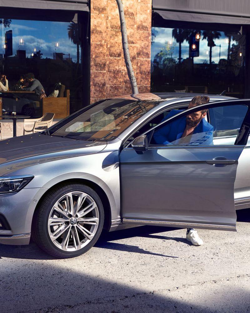 """Volkswagen Passat Limousine Elegance in Pyrit-Silber mit Rad """"Verona"""", Seite-Front stehend, Mann steigt aus dem Auto aus"""