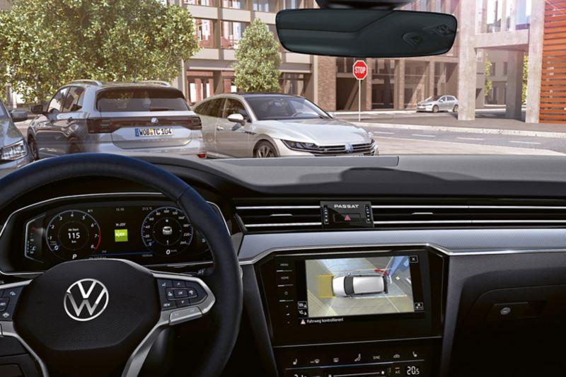 Système de vision périphérique Area View de la Passat, vue à travers le pare-brise sur une place de stationnement, et vue sur le poste de conduite avec l'écran Area View dans le système de navigation.