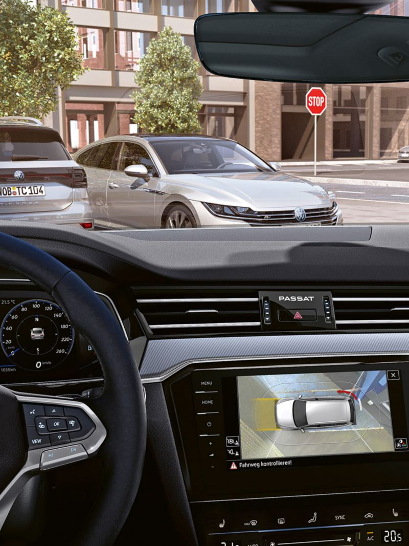 Vue périphérique «Area View» de la Passat, vue à travers le pare-brise jusqu'à un parking et vue sur le cockpit avec l'accent sur l'affichage «Area View» dans le système de navigation