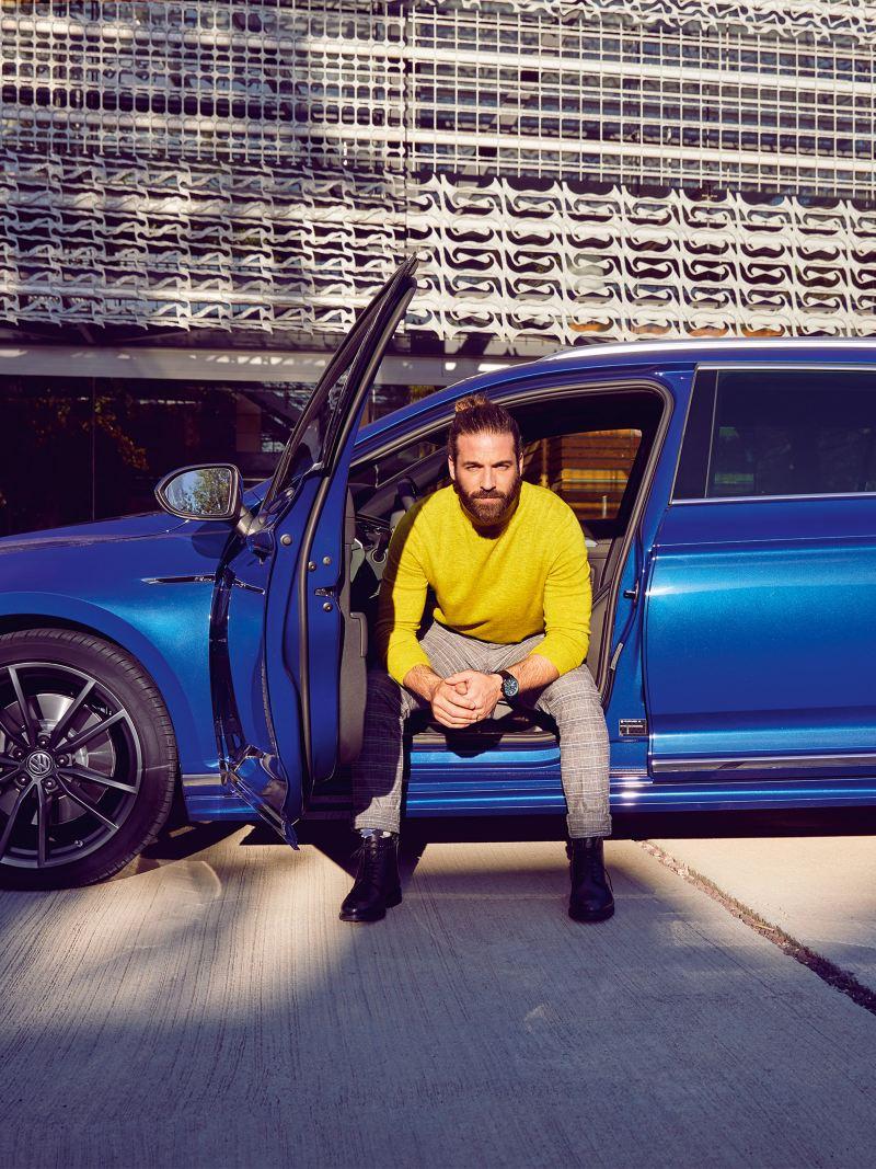 Un uomo è seduto al posto di guida di una Volkswagen Passat Variant, girato verso l'esterno, con la portiera aperta.