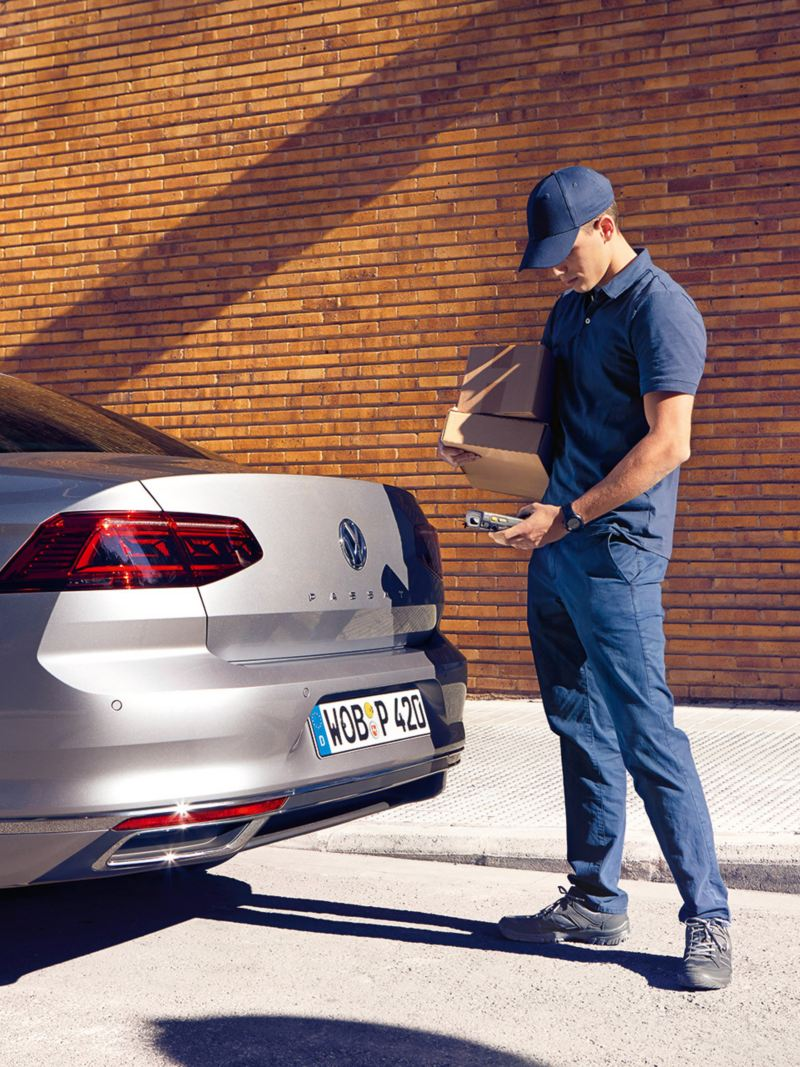 We Deliver: Deliverer stands at the rear of a Passat saloon and is about to open the luggage compartment flap with a smartphone.