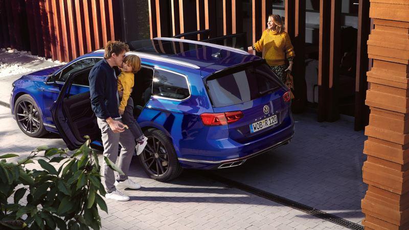 En familie står ved siden av VW Volkswagen Passat Stasjonsvogn