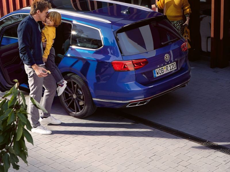 Vater trägt Sohn auf dem Arm vor einem VW Passat, Mutter im Hintergrund