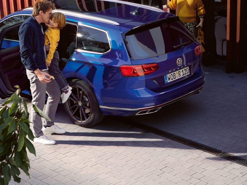 Eine Familie parkiert vor einem Haus mit dem VW Passat Variant