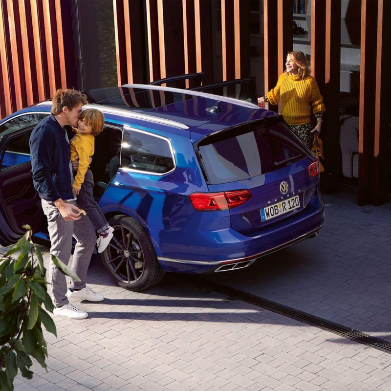 Una famiglia scende da Volkswagen Passat, vista 3/4 posteriormente dall'alto, parcheggiata fuori da un edificio.