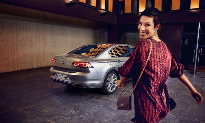 Seitliche Heckansicht eines neuen Passats, Frau läuft  auf das Auto zu und dreht sich dabei lächelnd um zur Kamera