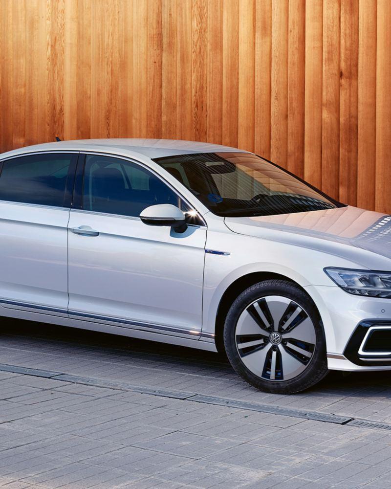 """VW Passat GTE Seitenansicht auf Parkplatz vor Holzwand und Lamellenwand, Felge """"Montpellier"""", Lackierung Oryxweiß Perlmutteffekt"""