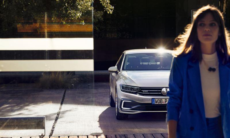 """VW Nuova Passat GTE: vista laterale/posteriore in un parcheggio, davanti a una parete di legno e una lamellare, cerchi """"Montpellier"""", verniciatura Oryx White effetto madreperla"""