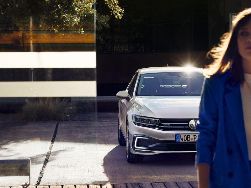 """Nuova Passat GTE: vista laterale/posteriore in un parcheggio, davanti a una parete di legno e una lamellare, cerchi """"Montpellier"""", verniciatura Oryx White effetto madreperla"""