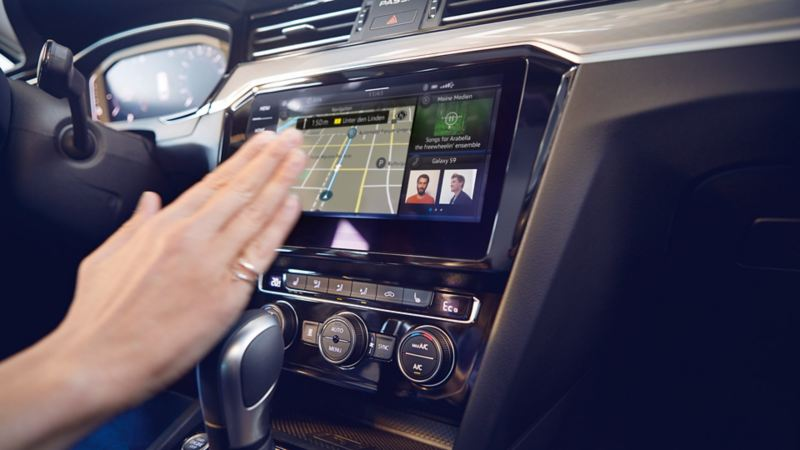 """Passat, sistema di navigazione """"Discover Pro"""", vista in obliquo da destra, visualizzazione suddivisa, con voci della rubrica, sistemi multimediali e navigazione, mano destra della conducente rivolta verso lo schermo per un comando gestuale"""