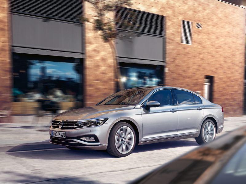 VW Passat in Silber fährt an einem Gebäude in der Stadt vorbei, 3/4 Frontansicht.
