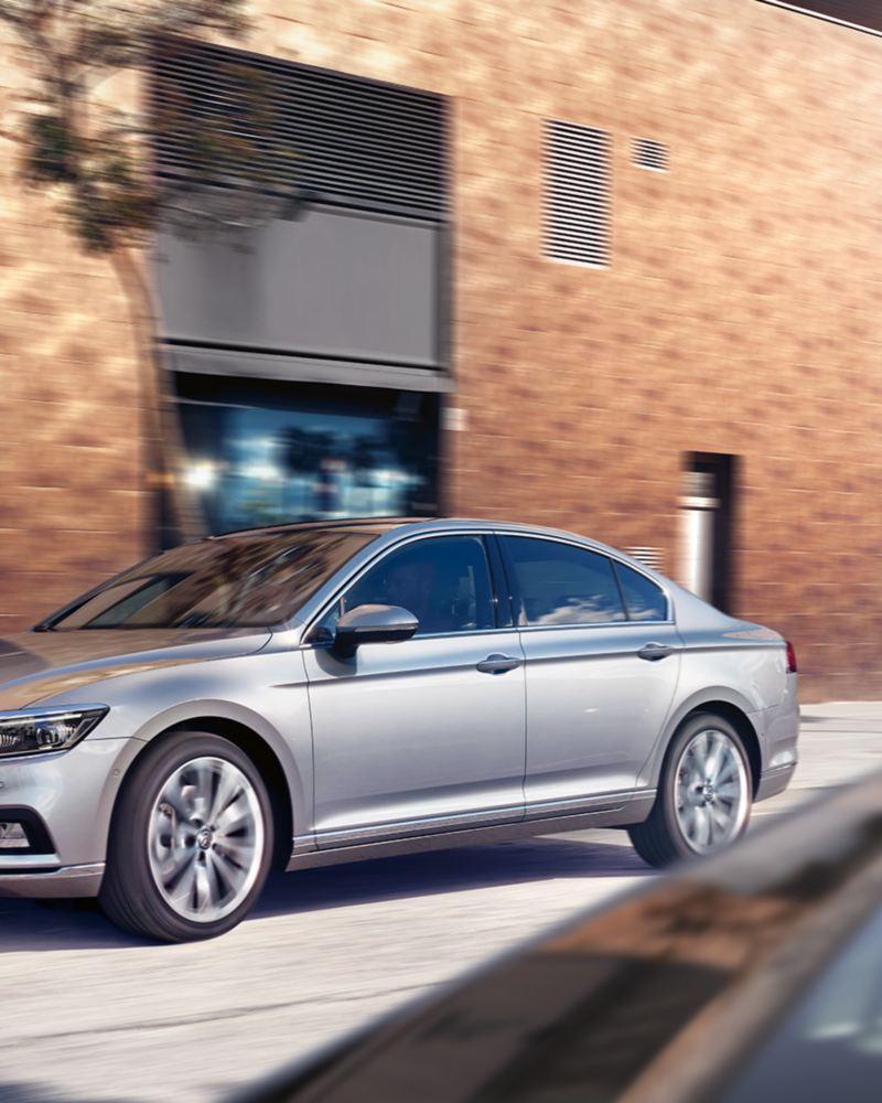 VW Passat fährt an einem Gebäude in der Stadt vorbei, 3/4 Frontansicht.