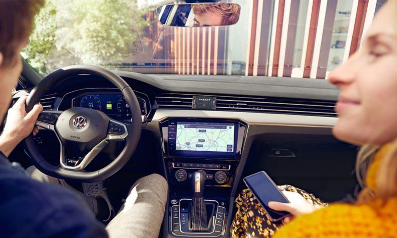 Mann und Frau mit Smartphone sitzen im Volkswagen
