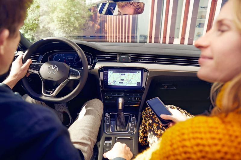 """Blick über die Schultern eines jungen Mannes und einer jungen Frau in das Cockpit des Passat, im Mittelpunkt das Navigationssystem """"Discover Pro"""", die Frau hält ein Smartphone in der Hand"""