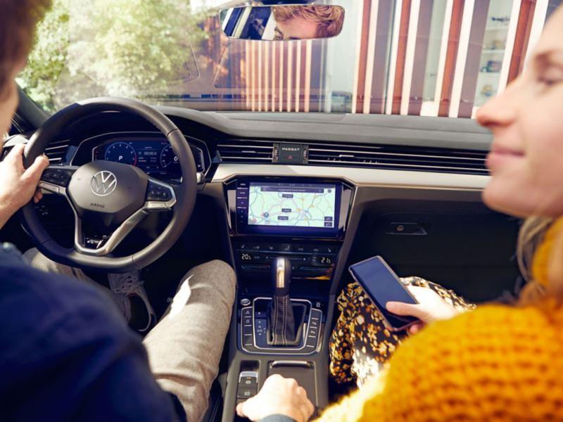 """Vista sobre os ombros de um rapaz e de uma rapariga no cockpit do Passat, no centro vê-se o sistema de navegação """"Discover Pro"""", a mulher tem um smartphone na mão."""