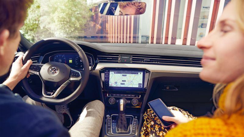 Mężczyzna i kobieta siedzą w VW Passat. Na komputerze pokładowym widać system Infotainment