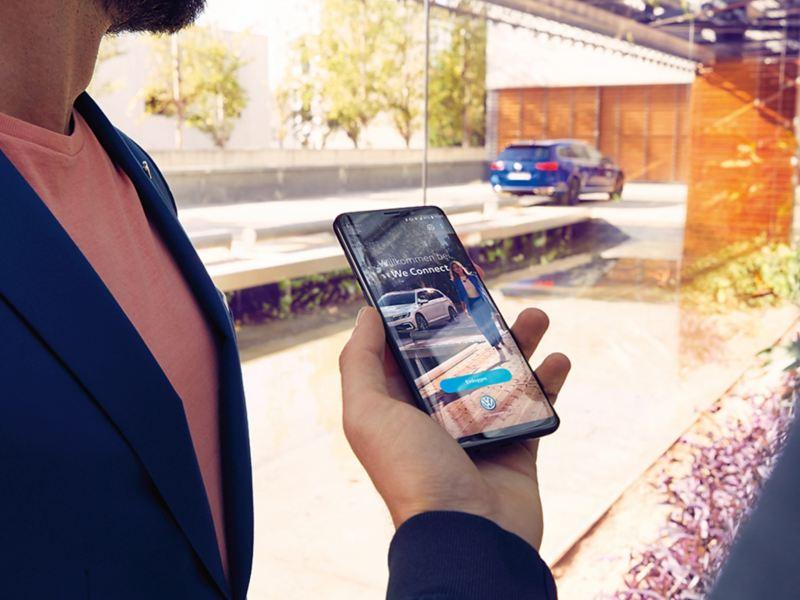Handy mit We Connect Dienst, Mann daneben, VW Passat im Hintergrund