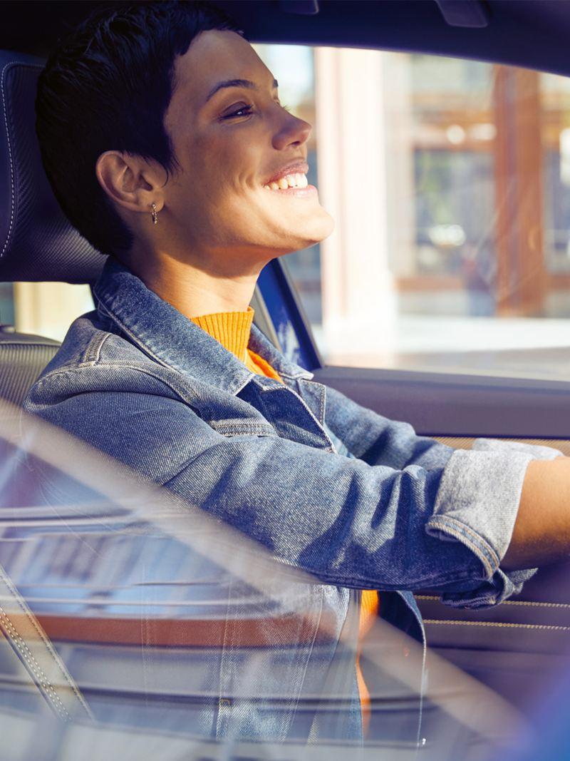 Frau sitzt am Steuer eines VW Passat Variant, Blick durchs geöffnete Beifahrer-Fenster