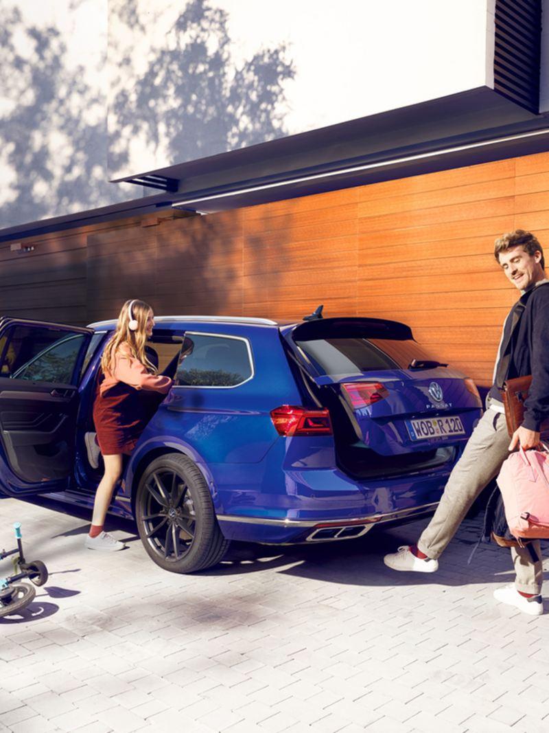 """Volkswagen Passat, """"Easy Open"""", vista posteriore di tre quarti, un uomo apre il portellone del bagagliaio con un movimento del piede (calcio) sotto il posteriore"""