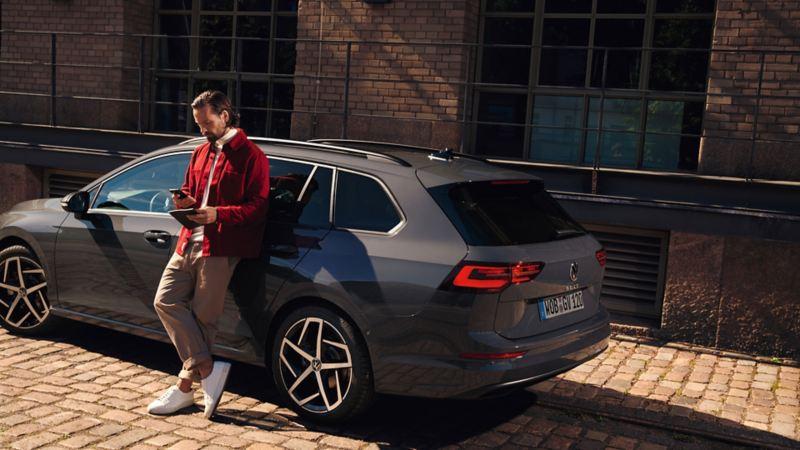 Ein silberner VW Passat GTE, im Vordergrund eine Frau im blauen Businessanzug.