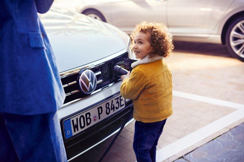 Bambina che inserisce il connettore nella presa situata nel frontale di Volkswagen Passat Variant GTE per ricaricare l'auto