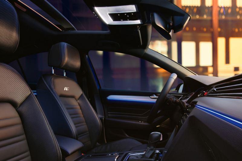 Volkswagen Passat R-Line Εσωτερικό-Λήψη των μπροστινών καθισμάτων πλευρικά προς την κατεύθυνση του αριστερού παραθύρου, ο φωτισμός περιβάλλοντος φωτίζει στην οροφή, στην πόρτα και στον πίνακα οργάνων